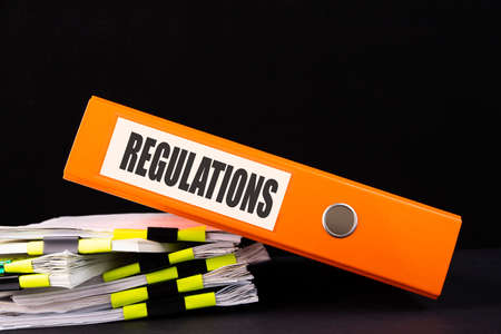 Regulations word on folder on a black background with documents. Business and finance concept.