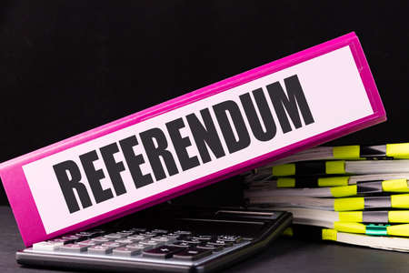 REFERENDUM text is written on a folder lying on a stack of papers on an office desk. Business concept. 스톡 콘텐츠