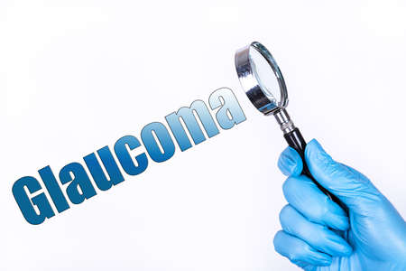 GLAUCOMA text written on the background of a magnifying glass in the doctor hand in a medical glove. Medical concept. Stock Photo