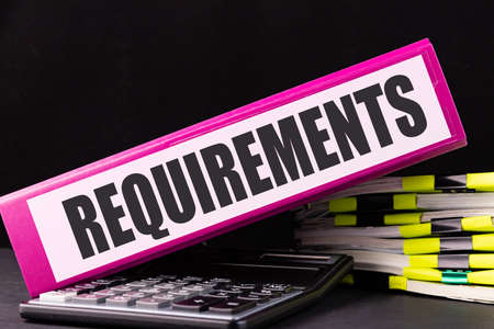 REQUIREMENTS text is written on a folder lying on a stack of papers on an office desk. Business concept. Stok Fotoğraf