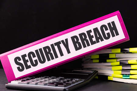 SECURITY BREACH text is written on a folder lying on a stack of papers on an office desk. Business concept.