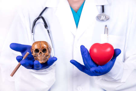 Medical concept choice smoking or life. The doctor holds a heart in one hand and a skull and a cigarette in another.
