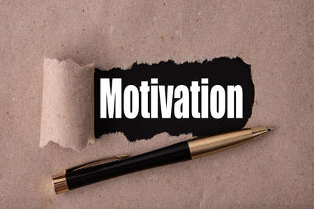 MOTIVATION text written under torn paper and a recumbent metal pen. Business strategy concepts.