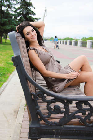 Beautiful, young dark-haired girl in a summer dress sitting on a bench 免版税图像 - 151123397