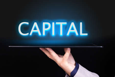 Man hand holds a tablet over which a neon text is written, the word CAPITAL. Business concept.