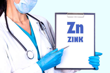 Zn ZINK text is written on a tablet that is held by a doctor in medical clothes and disposable gloves. Medical concept. 스톡 콘텐츠