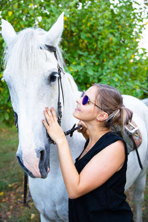 Beautiful, young girl riding a horse, country style.