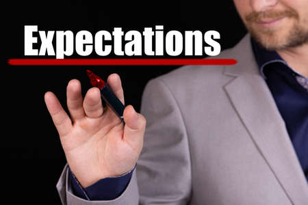 Businessman, man writes marker text on the word EXPECTATIONS. Business concept, stteryria.