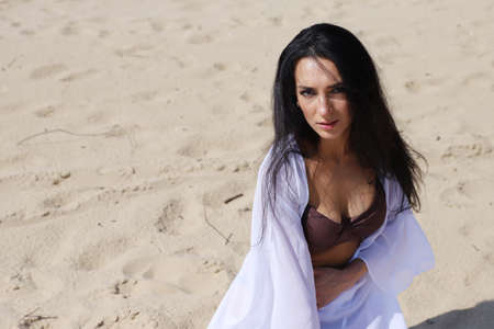 Beautiful dark-haired girl in a swimsuit on the beach. Portrait, posture, look.