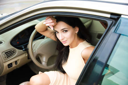 Beautiful dark-haired girl in the car. Portrait, posture, look.
