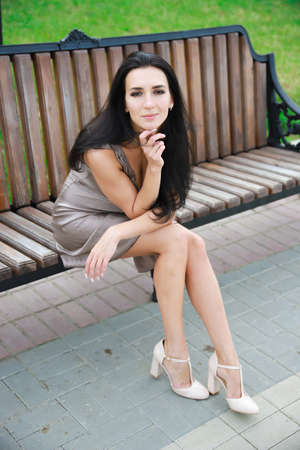 Beautiful, young dark-haired girl in a summer dress sitting on a bench Imagens