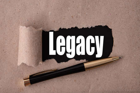 LEGACY text written under torn paper and a recumbent metal pen. Business strategy concepts. 写真素材