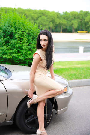 Beautiful young girl on a background of a car and a key for spinning wheels.