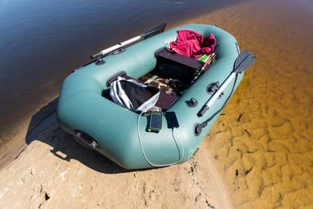 Rubber boat with fishing tackle standing on a river near a sandy beach. Mobile phone offline charging concept. Reklamní fotografie