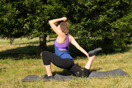 Female fitness instructor does, shows exercises in a green park. Sport concept.