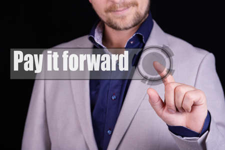 Businessman presses a button with the text PAY IT FORWADR. Business concept.