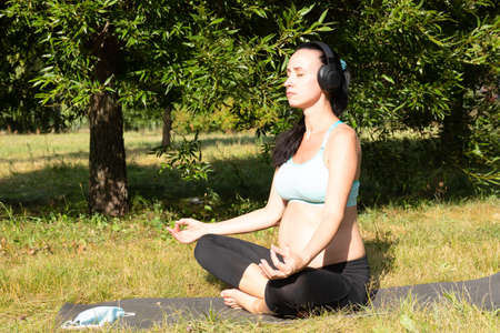 A pregnant woman is engaged in meditation in the park, listening to music on headphones. High quality photo