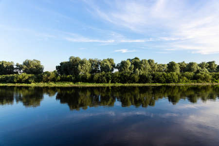 European landscape, river, blue sky on a background of green trees.