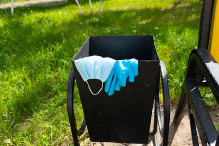 Thrown away medical gloves and protective masks in the trash bin after quarantine. Recycling and ecology concept.