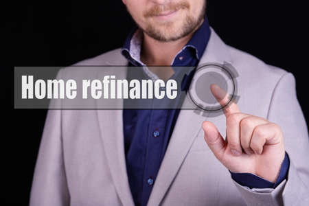 Businessman presses a button with the text HOME REFINANCE. Business concept. 스톡 콘텐츠