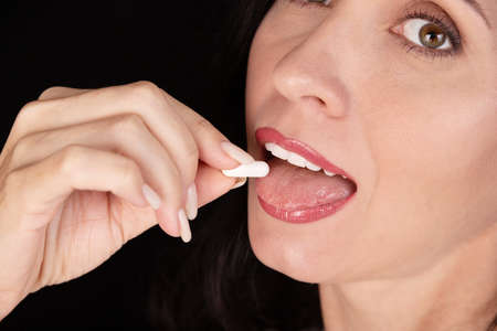 White oval tablet, capsule on the tongue of a girl, woman, close-up. Placebo concept.
