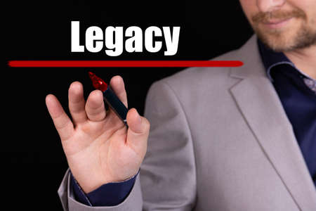 Businessman, man writes marker text on the word LEGACY. Business concept, stteryria.