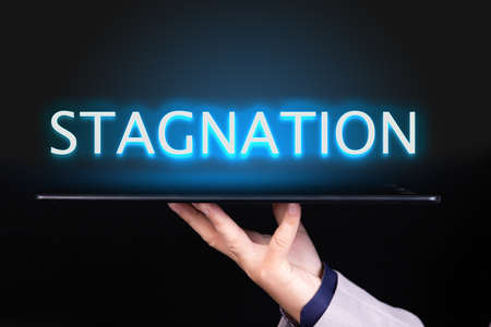 Man hand holds a tablet over which a neon text is written, the word STAGNATION. Business concept.