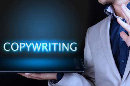 Businessman, man holds in his hand a tablet with a neon word, COPYWRITING text. Business concept. 스톡 콘텐츠