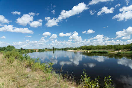 Landscape River with blue sky and clouds is reflected in the water on a summer day.