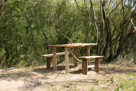 Homemade wooden table with chairs green grass family vacation, picnic, woodland, river.