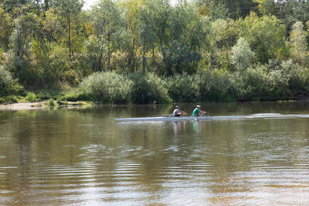 A couple of young people are sailing along the river in a kayak. 스톡 콘텐츠
