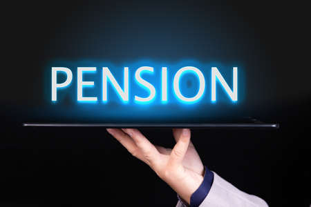 Man hand holds a tablet over which a neon text is written, the word PENSION. Business concept.