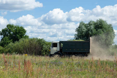 Truck loaded with millet in the countryside, driving across the field. 版權商用圖片