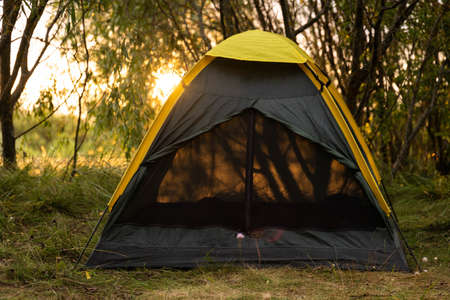 Summer tourist tent on a background of nature. The concept of travel and outdoor activities. 스톡 콘텐츠