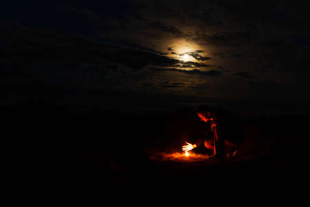 A man sits on against a burning candle on a dark night. Mystic concept.