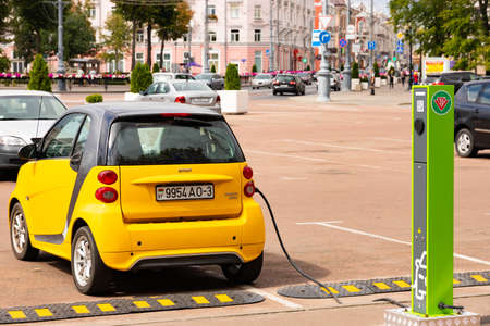 MINSK, BELARUS - AUGUST 23 2020: Electric vehicle charging station with power plug for electric vehicles. The concept of ecology and environmental pollution by car emissions. Redakční