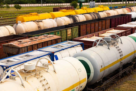 Tanks with fuel, wagons with cargo at a freight railway station. Logistics and transportation concept. Stock Photo