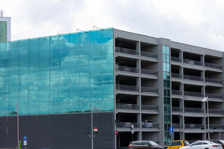 Multi-level modern car park made of glass and concrete.