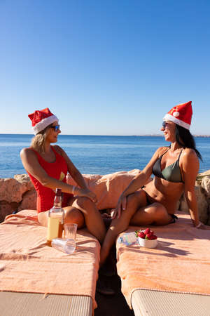 Two women in bathing suits and red Christmas hats celebrate Christmas and New Year on the Red Sea beach. Archivio Fotografico - 155109345