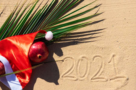 Hat of Santa Claus on the background of a palm leaf, with pomegranate fruits on the sandy beach of the Red Sea. Tropical Christmas card.