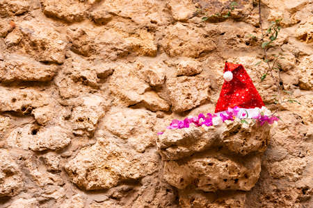 Tropical Christmas and New Year in the desert, an oasis. Santa Claus hat on the Wall ledge of marine, sandy sediments. Archivio Fotografico