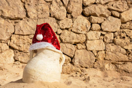 Tropical Christmas and New Year in the desert, an oasis. Santa Claus hat is worn on an antique vase, jug. Archivio Fotografico