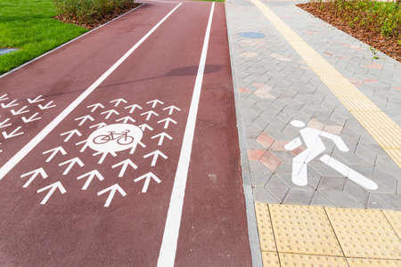 New groomed wide modern bike and pedestrian paths two lanes of opposite directions. Bicycle lanes with road markings in the summer city center. Archivio Fotografico