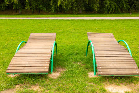 Wooden deck chairs line the green grass under the sun