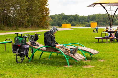 Minsk, Belarus - September 05, 2020: A tourist on a bicycle stopped to rest on a sun lounger, read a book. Editoriali