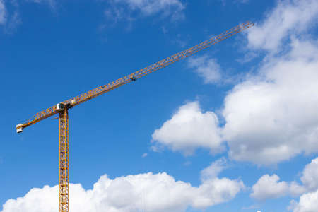Tower construction crane on a background of blue sky with clouds