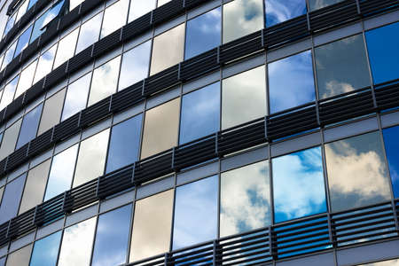 Clouds reflected in windows of modern office building Archivio Fotografico