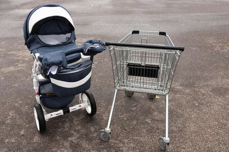 An empty grocery cart from a supermarket on the street and a baby carriage. Concept.