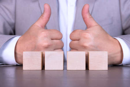 A businessman adds four wooden cubes with empty space for icons, free space for letters, numbers, symbols or labels. Stock Photo