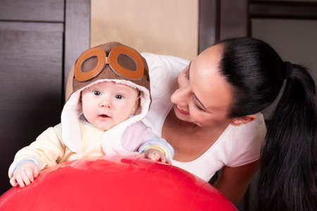 Aviator kid, in a pilot hat, together with a beautiful young mother, close up portrait. Banco de Imagens